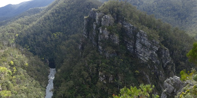 Layered white cliffs above river flowing through gorge