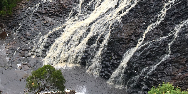 Photograph of water flowing across a sloping surface of basalt columns.