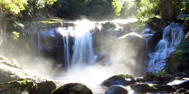 Photograph of short waterfall in bright sunlight.
