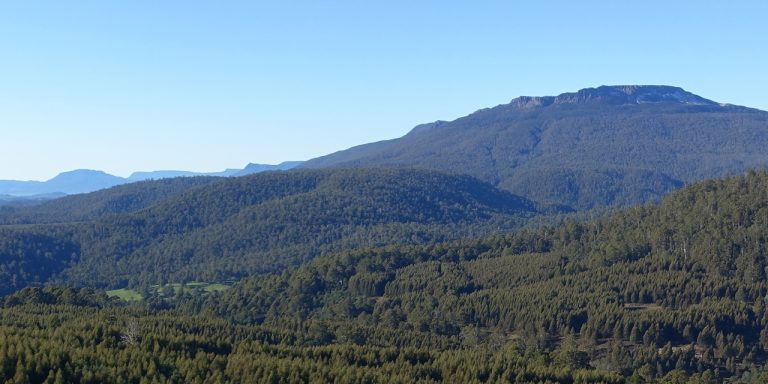 Photograph of line of mountain bluffs under a clear blue sky.