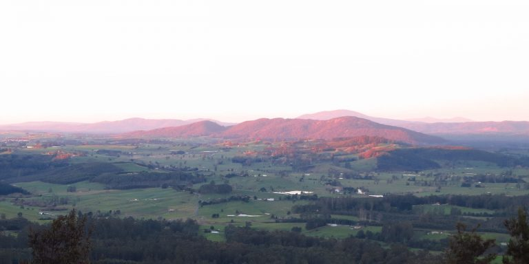 Photograph of low mountain tinted pink by sunset.