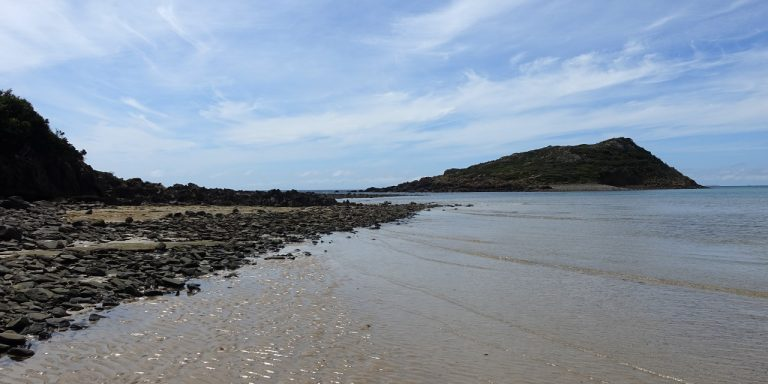 Photograph of beach with rocky point on the left and small island on the right.